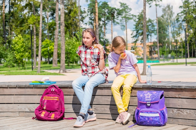 Crianças em idade escolar almoçando juntas fora do prédio. meninas no jardim compartilhando o almoço