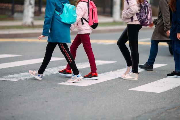 Crianças em idade escolar atravessam a rua com máscaras médicas. as crianças vão à escola.