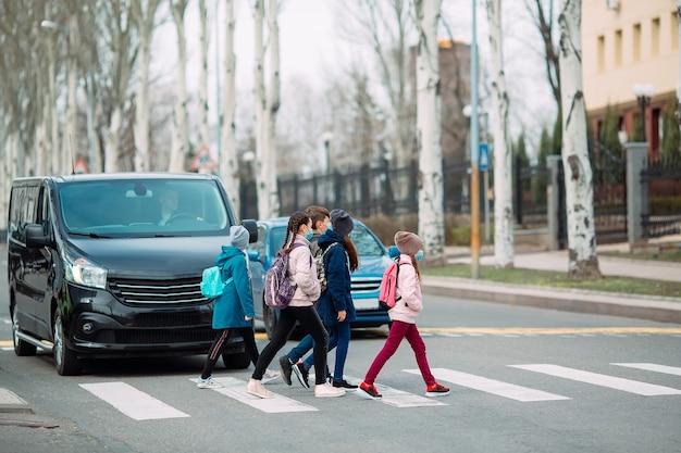 Crianças em idade escolar atravessam a rua com máscaras médicas