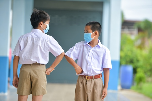 Crianças em idade escolar com máscara de proteção contra o vírus da gripe na aula em sala de aula