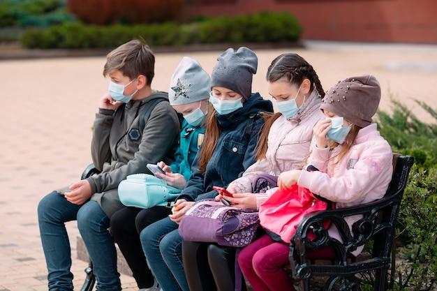 Crianças em idade escolar com máscaras médicas sentam em um banco