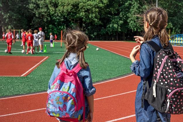 Crianças em idade escolar com mochilas no estádio, vendo os meninos jogarem futebol.