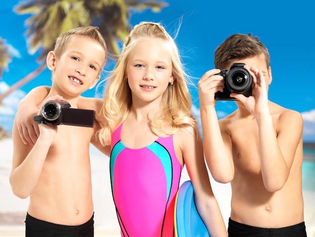 Crianças em idade escolar em pé com uma câmera fotográfica e de vídeo nas mãos.