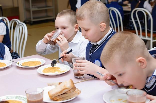 Crianças em idade escolar estão almoçando em uma mesa no refeitório da escola