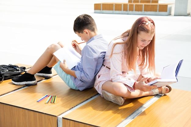 Crianças em idade escolar, menina e menino, adolescentes de 11 anos de idade estudam no pátio da escola, sentam no banco do pátio da escola, leem um livro e escrevem no caderno