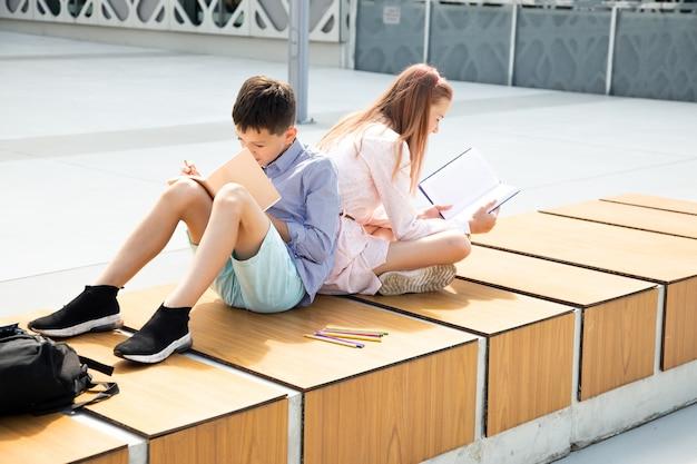 Crianças em idade escolar, meninas e meninos, adolescentes de 11 anos, estudam no pátio da escola, lêem livros e escrevem em um caderno