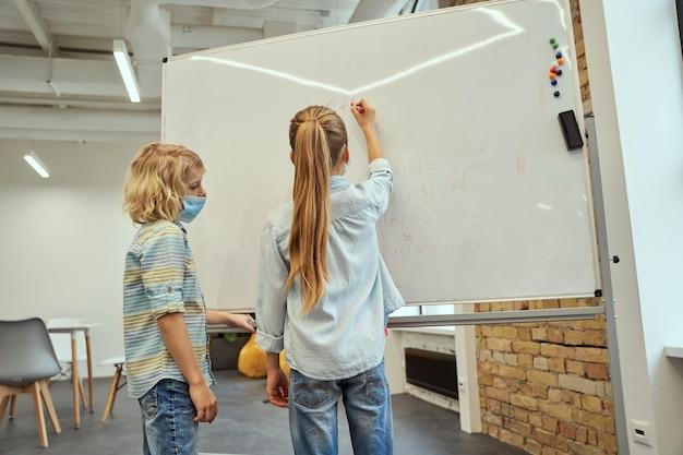 Crianças em idade escolar, menino e menina, usando máscara protetora durante a pandemia de coronavírus, escrevendo sobre