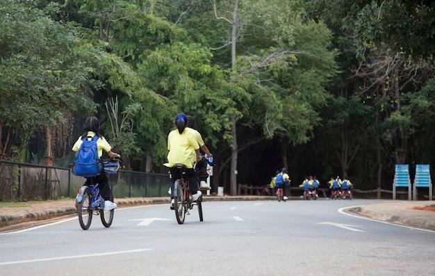 Crianças em idade escolar passeando de bicicleta pelo estacionamento para aprender sobre o parque natural