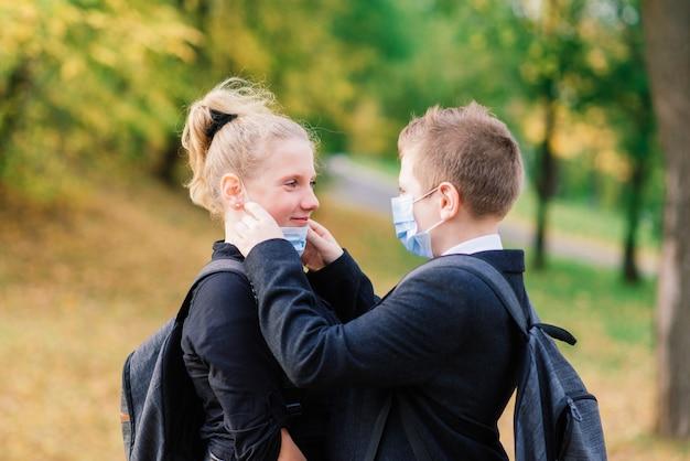 Crianças em idade escolar, um menino e uma menina com máscaras médicas andam no parque da cidade.
