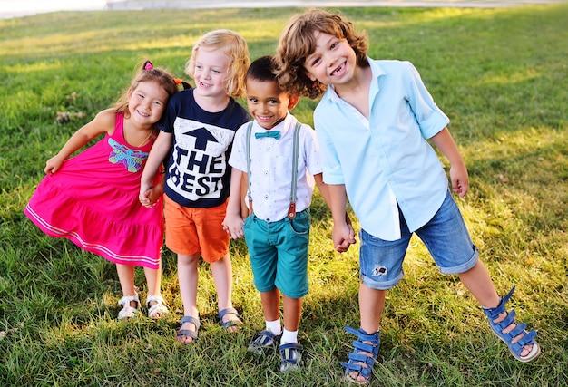 Crianças em idade pré-escolar brincando no parque na grama