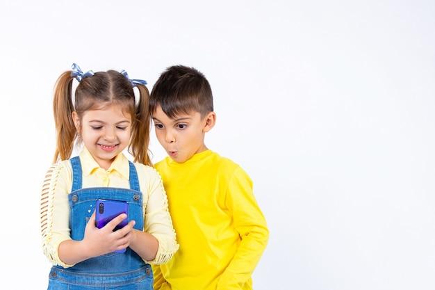 Crianças em idade pré-escolar estão assistindo a algo em um smartphone.