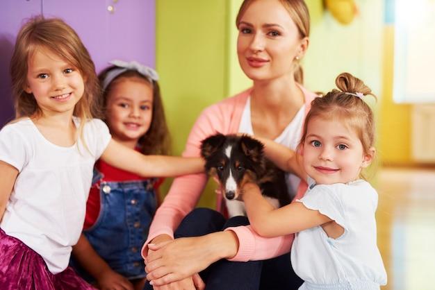 Crianças em idade pré-escolar se divertindo com o cachorro