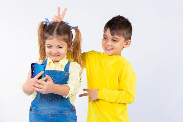Crianças em idade pré-escolar tiram uma selfie em um smartphone. o menino dá chifres na menina.