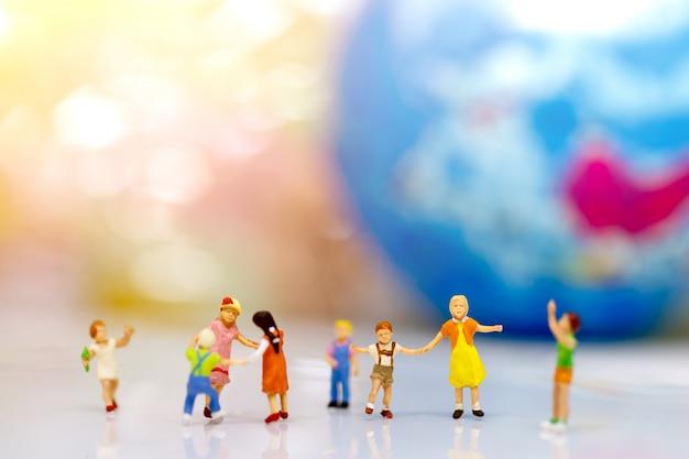 Crianças em miniatura, de mãos dadas com o globo
