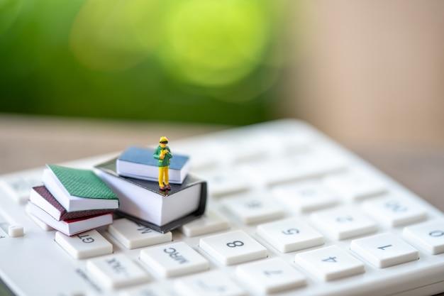 Crianças em miniatura pessoas em pé em livros e calculadora branca