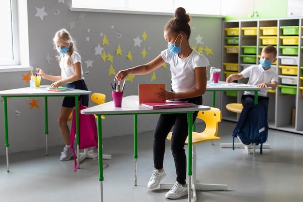Crianças em pé ao lado de suas mesas enquanto usam máscaras médicas