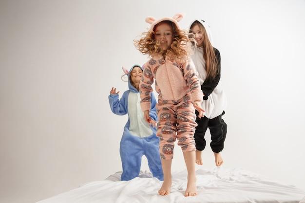Crianças em pijamas quentes e macios fazendo festa coloridas alegres brincando em casa