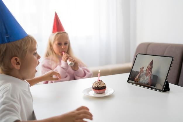 Crianças em quarentena em casa comemorando aniversário com um tablet