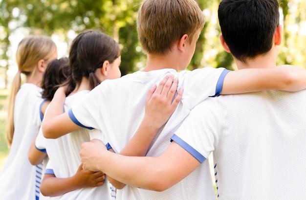 Crianças em roupas esportivas abraçadas