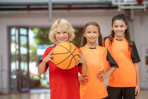 Crianças em roupas esportivas em pé com uma bola e parecendo curtidas