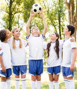 Crianças em roupas esportivas jogando futebol