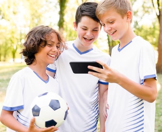 Crianças em roupas esportivas olhando para um telefone