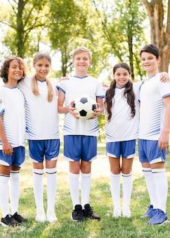 Crianças em roupas esportivas posando com uma bola de futebol