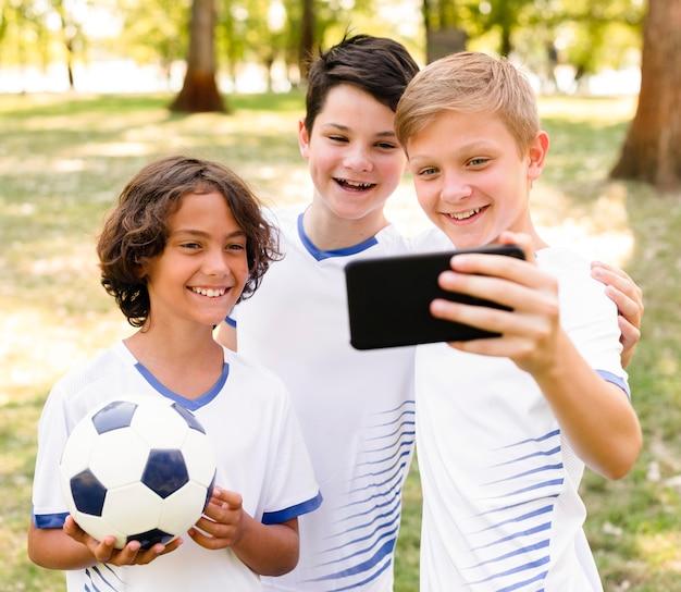 Crianças em roupas esportivas tirando uma selfie