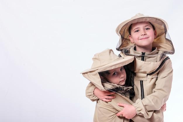 Crianças em ternos de apicultor, posando em fundo branco do estúdio.