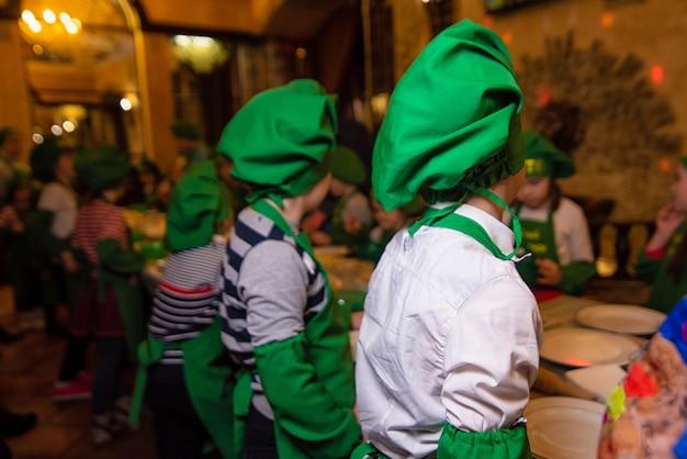 Crianças em ternos verdes de cozinheiros e bonés verdes estão em uma fileira