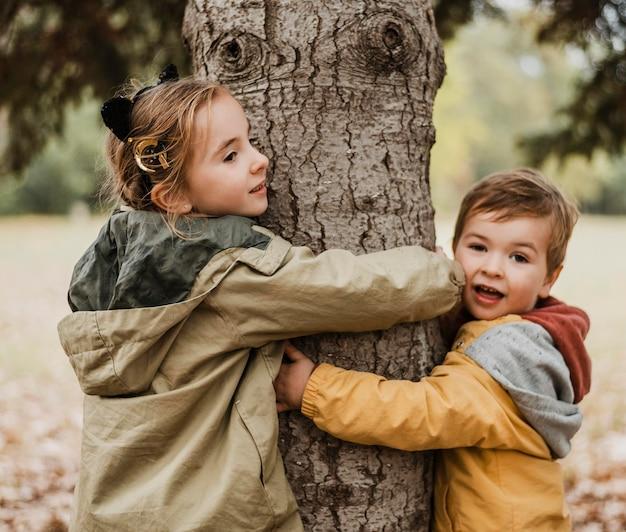 Crianças em tiro médio abraçando uma árvore