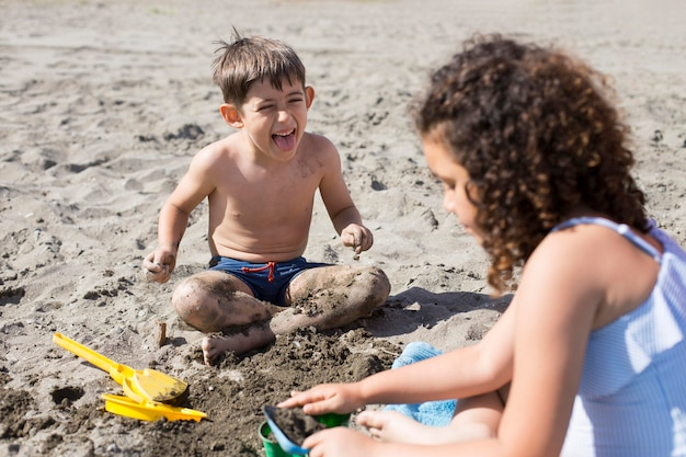 Crianças em tiro médio brincando na praia
