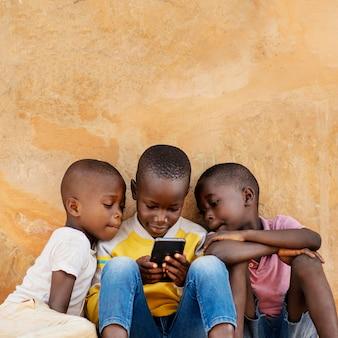 Crianças em tiro médio olhando para smartphone