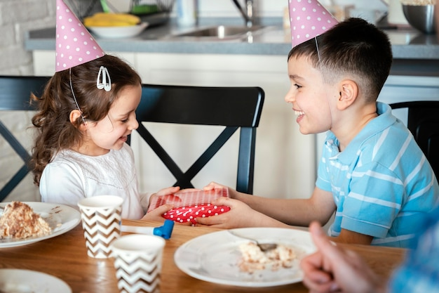 Crianças em tiro médio usando chapéus de festa