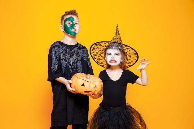 Crianças em trajes de halloween, brincando com abóbora