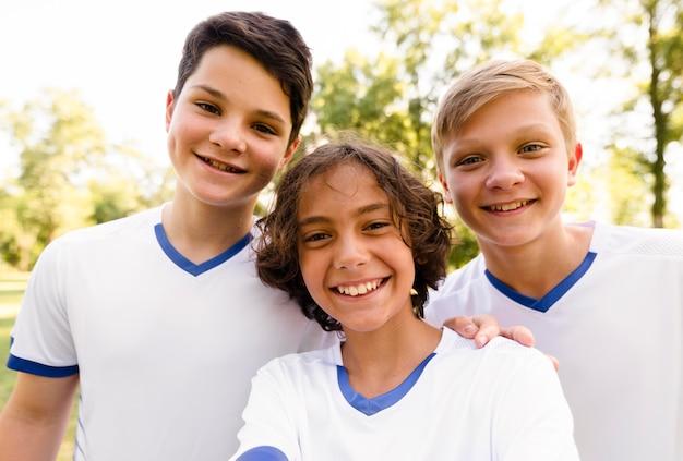 Crianças em trajes esportivos de futebol sorrindo