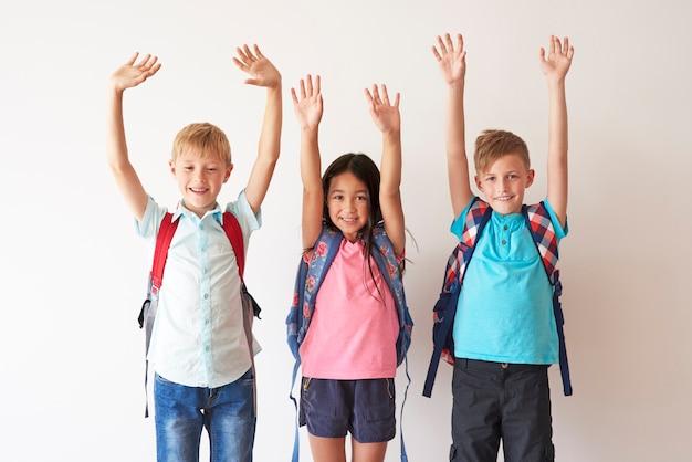 Crianças em um fundo branco com as mãos para cima