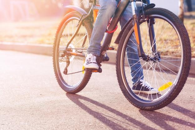 Crianças em uma bicicleta na estrada asfaltada no dia de verão do amanhecer.
