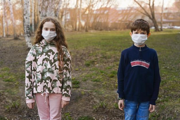Crianças em uma máscara médica ao ar livre.