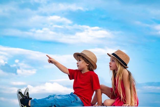 Crianças encantadoras no fundo do céu, menina bonitinha e menino posando emoções externas no rosto infantil.