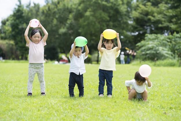 Crianças enfileiradas com balões na grama