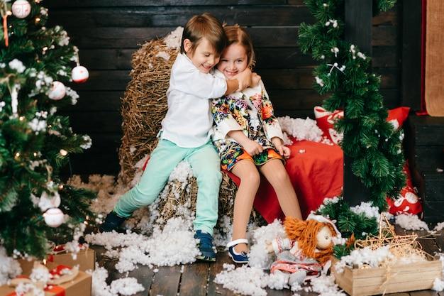 Crianças engraçadas abraçando no estúdio com árvore de natal e decorações de ano novo.