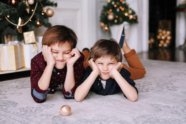 Crianças engraçadas ao lado da árvore de natal brincando e se divertindo juntos