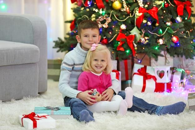Crianças engraçadas com caixas de presente e árvore de natal