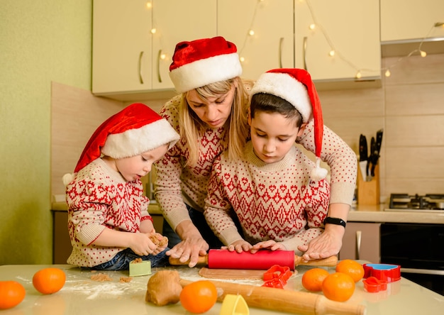 Crianças engraçadas e mãe cozinhando biscoitos de natal em casa. mãe e filhos fazendo casa de pão de gengibre.