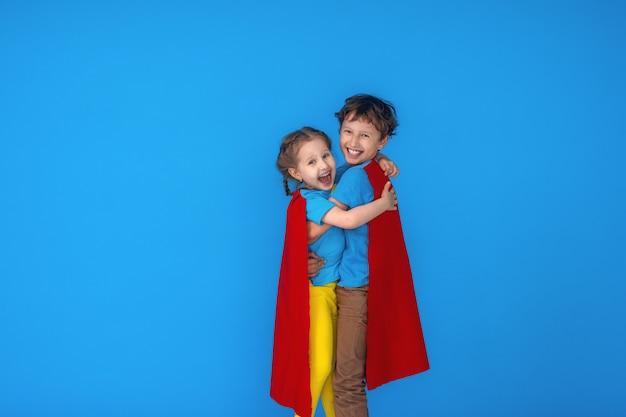 Crianças engraçadas é o herói da super força na capa e máscara vermelhas. super-herói do conceito.