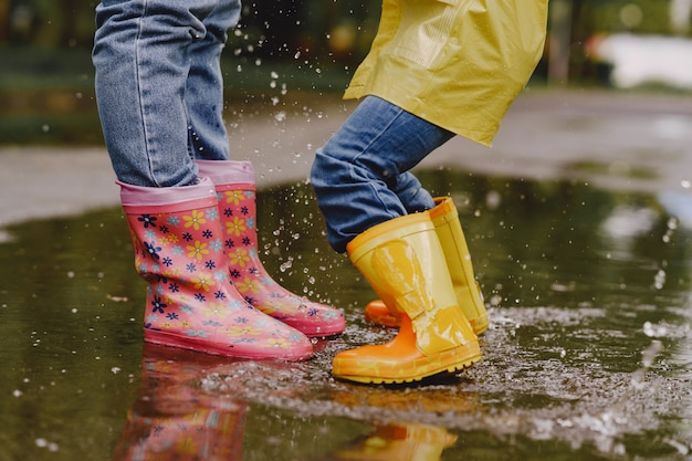 Crianças engraçadas em botas de chuva brincando com navio de papel por uma poça