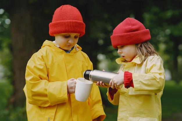 Crianças engraçadas em botas de chuva, jogando em um parque chuvoso