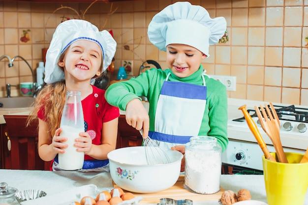 Crianças engraçadas família felizes estão preparando massa, assar biscoitos na cozinha