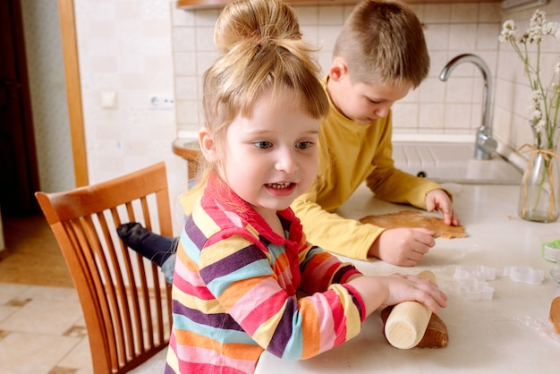 Crianças engraçadas fazem biscoitos na cozinha. família feliz.